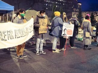protestors holding justice for abdi signs and defund the police signs at night during a major intersection blockade